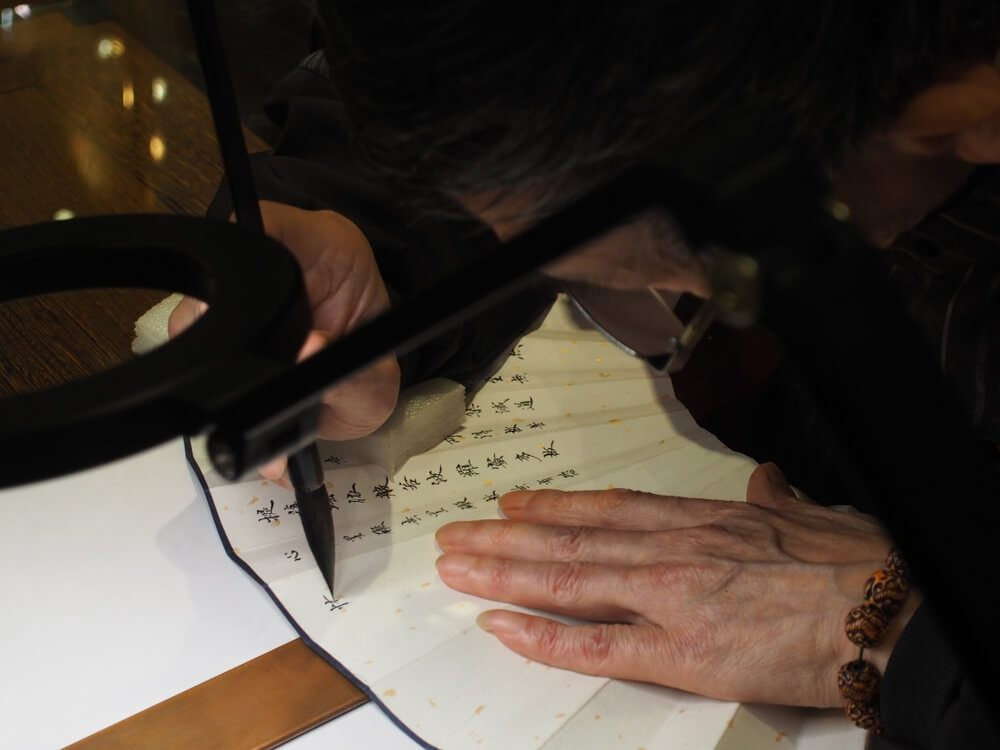 A calligraphy master is expertly writing calligraphies on a paper fan